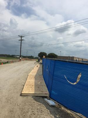 Wind screen installed on fences at student walkway.  Wooden walkway being built by carpenters to keep students from walking in mud.