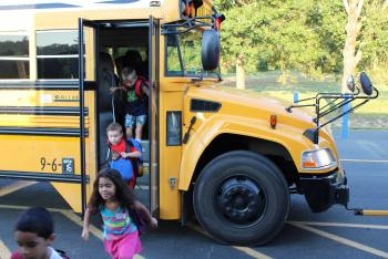 Students unloading off bus on first day of school.