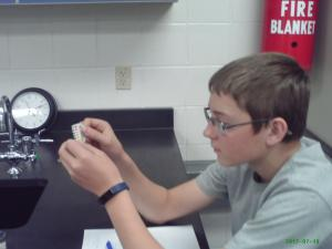 Students dip pH paper in solutions and determine if acid or base
