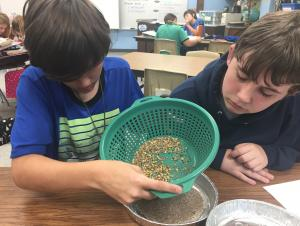Matthew and Zane separating sand and pebbles