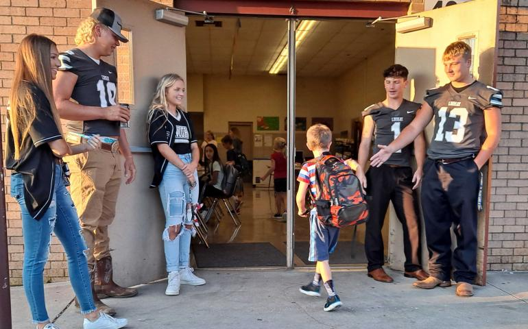 High School kids greeting little kids in cafeteria.