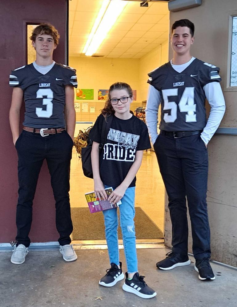 Football players greeting elementary kid.