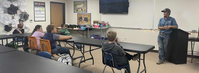 Garrett Lee speaks to seventh graders about the fish business.