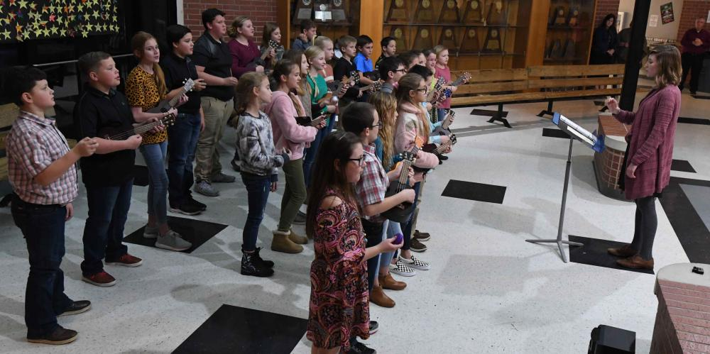 elementary students singing for the school board