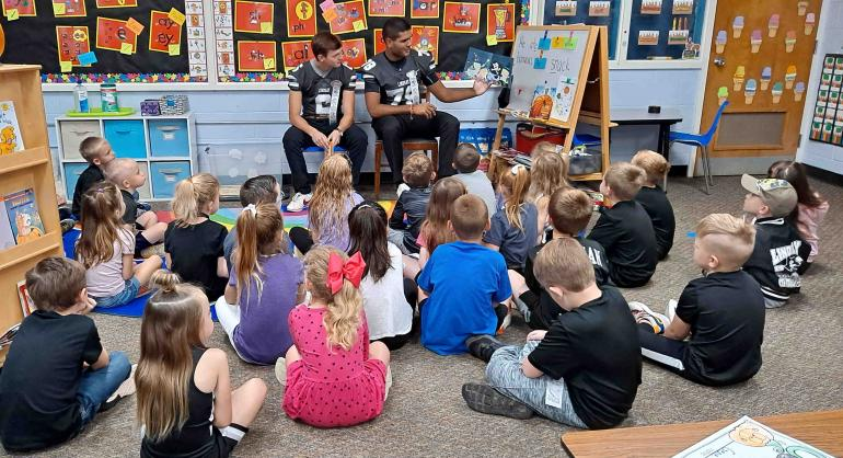 Coltan and Yosh read to kindergarteners.