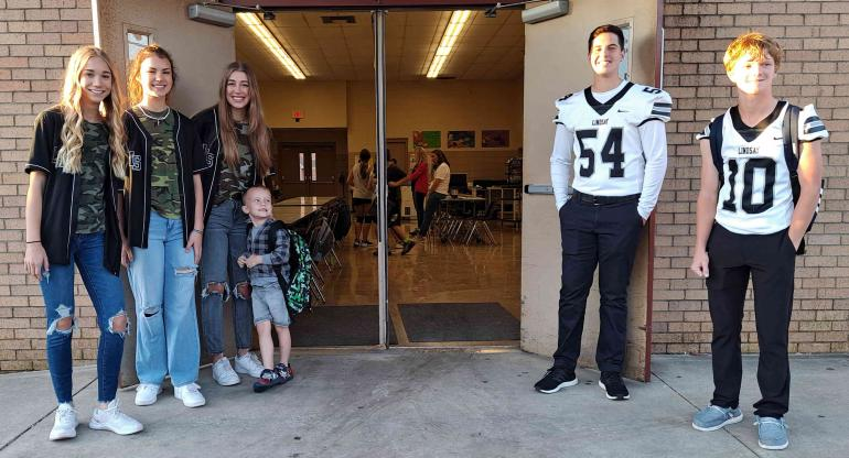 Cheerleaders and football players welcome elementary students