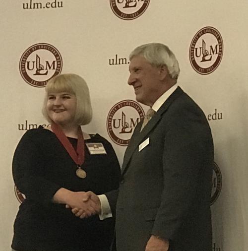 Arabella Jennings shaking hands with ULM President Nick Bruno
