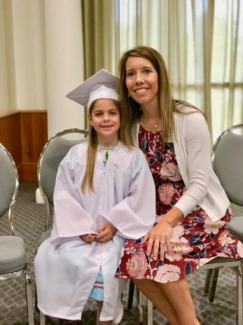 Teacher poses with young girl UVA Kindergarten Graduate of 2018