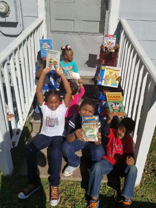 children sitting on outside stairs with their books at shu shu's depot