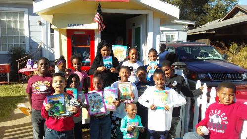 lots of children holding books for a picture in front of shu shu's depot