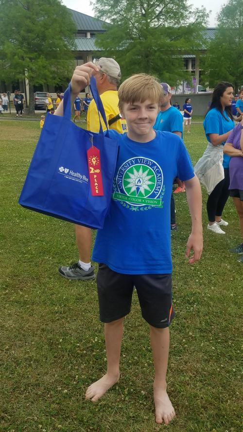 Young boy UVA student holds up his 2nd place ribbon at the Autism 5k
