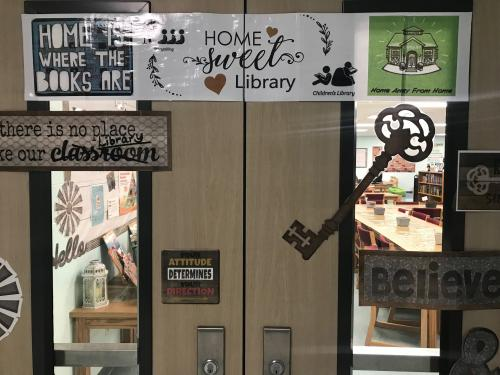 Library doors with home sweet home banner and decor.