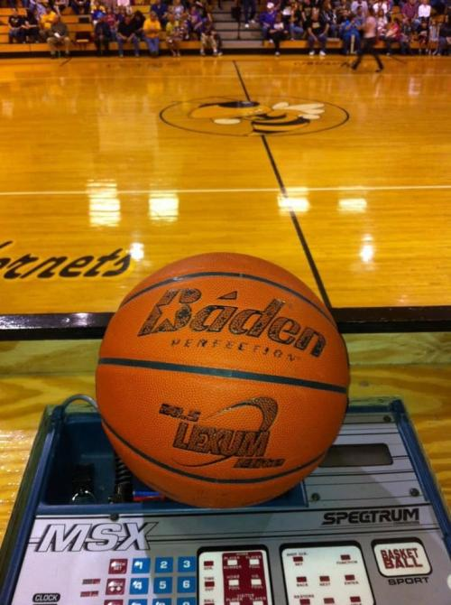 Basketball gym floor in background with Baden Basketball in focus.