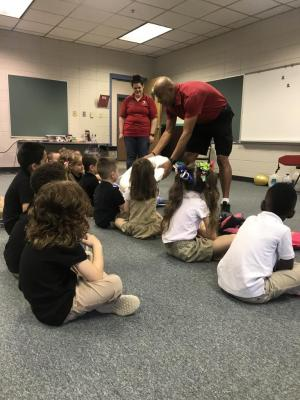 Lifeguards from the Fort Polk  demonstrate how to use a life vest to Mrs. Austin's Class.