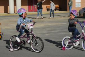 Students riding bikes and tricycles