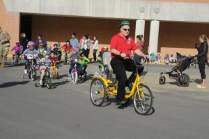 Mr. Corriell leads Students riding bikes and tricycles