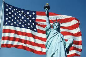 Picture of the Statue of Liberty in front of the American flag.