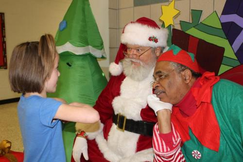 Justiss Elementary Kindergartner Joslynn Briggle shares with Santa, Tony Clark, and his elf, Robert High, what she would like for Christmas.