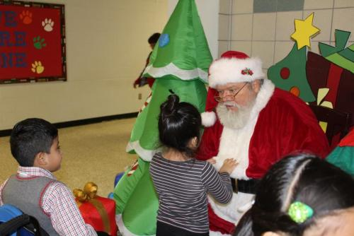Justiss Elementary Kindergartners Joel Barrios and Bianca Ortega visit with Santa, Tony Clark, before they get their picture made with him during his visit to Justiss.