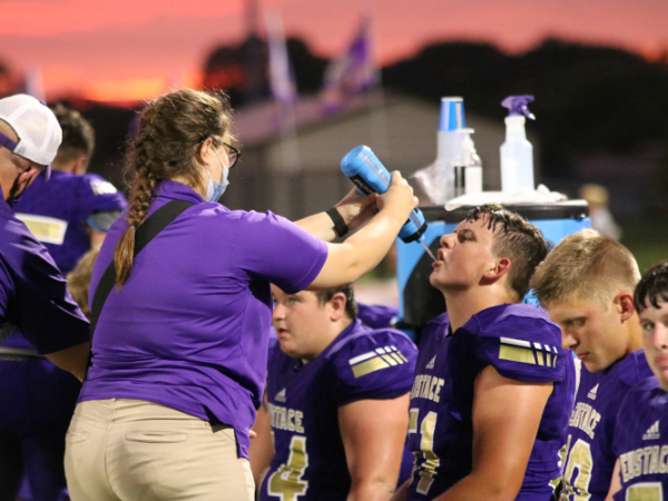 Trainer Kaylee McKee on the sidelines with Justin Henson Sept. 4.