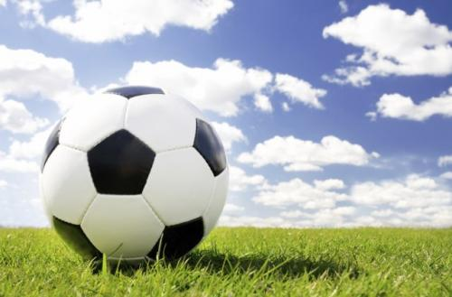 soccer ball on field with sky visible