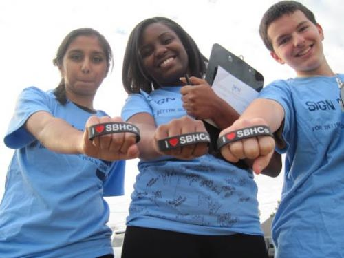 Picture of students holding a I love School Based Health Centers bracelet.