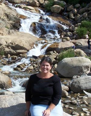 Mrs. Patterson sitting by a Rocky Mountain spring.