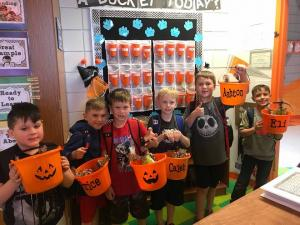 Boys showing off their Halloween treat buckets.