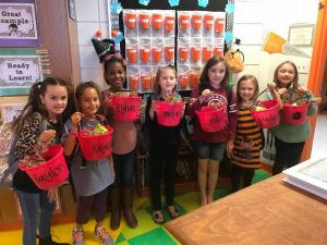 Girls showing off their Halloween treat buckets.
