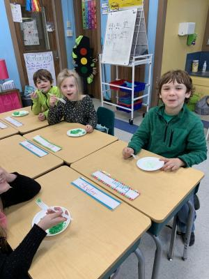 First grade students enjoying green eggs and ham during Read Across America Week.