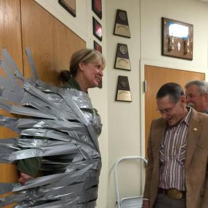 Students tape Mrs. Parchman to the wall for reaching AR School Goal!