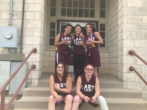 HS Track Girls Sitting on front Steps with awards