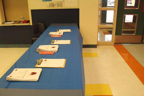 Table set up at entrance with sign in for parents and teachers and agenda/booklets.