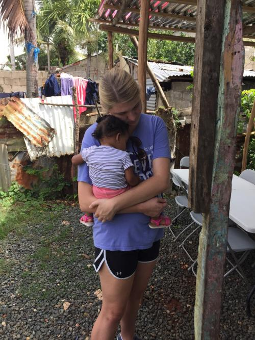 Girl holding a child on the mission field in Dominican Republic