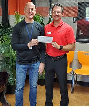 Jason Walter of Ross Downing Buick GMC presenting a check to Mr. Pellegrin
