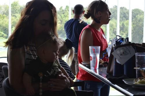 Mom holding her baby at the Top Golf event sitting in a chair