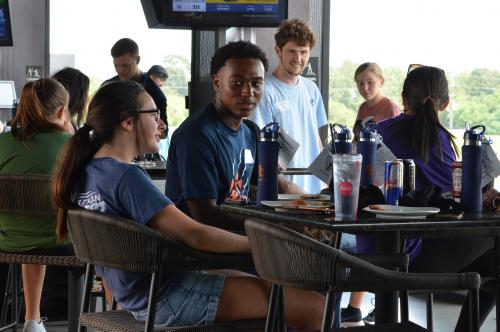 Students sitting in bay at Top Golf