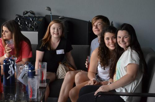 Students sitting in bay at Top Golf all smiling