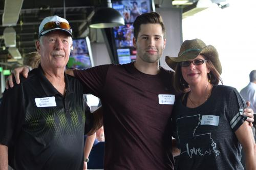 Family posing for pic at Top Golf event