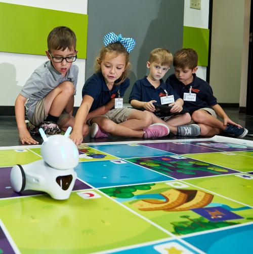 Young children working with a robot on a mat