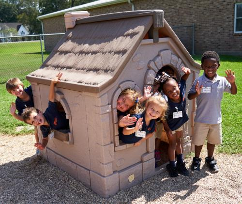 Young children huddled together in a playhouse waving at camera through the doors and windows smiling.