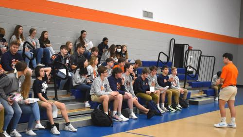 FCA Meeting in the Gym. Student presenting to audience seated in bleachers