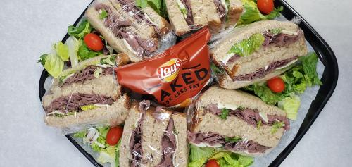 Platter of roast beef sandwiches with a bag of Lays baked potato chips in the center of the sandwiches