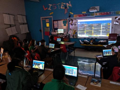 students with laptops in a classroom