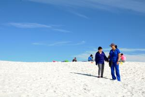 A student walks hand in hand with Registered Nurse Eva J. Gonzales as they head down the dune
