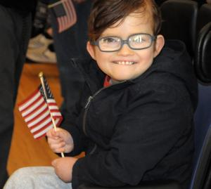 A student smiles as he holds the American flag