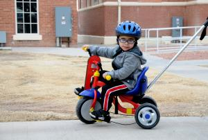 A student rides a tricycle outside.