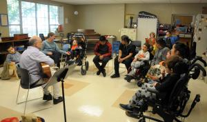 Music Instructor Carlos Cuellar plays the guitar as he leads students to sing.