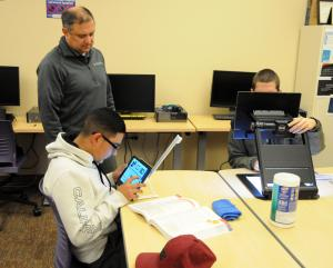 Students try out assistive technology devices as a representative from Nano Pac Inc watches