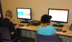 Students in the Tech Lab wearing headphones and using computers